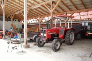 Ein roter Traktor in der Hofgarage
