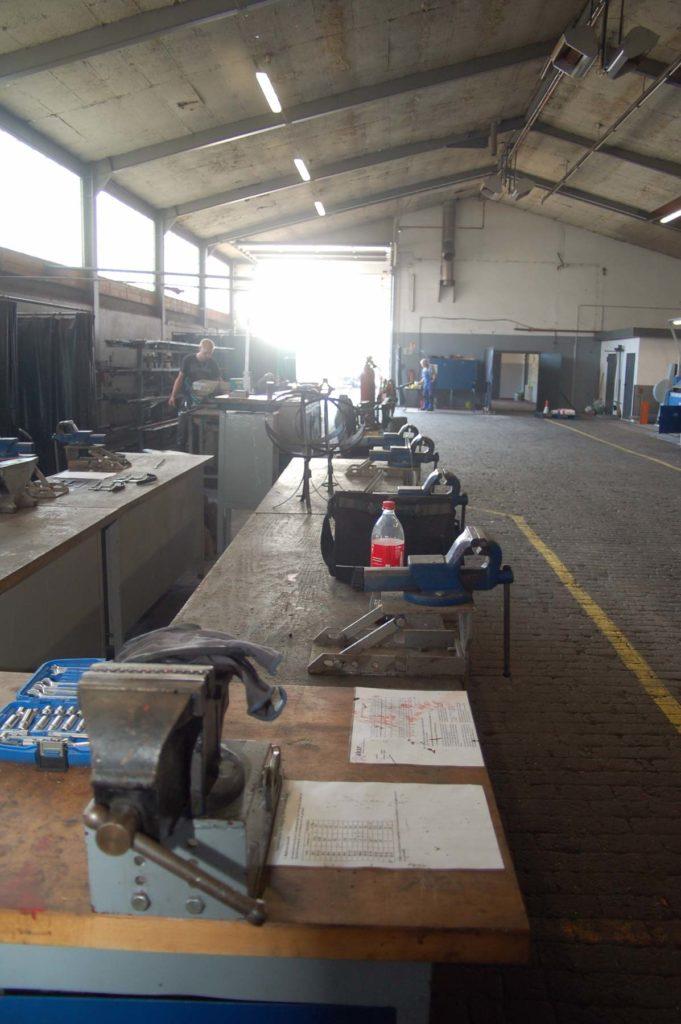 Ein Überblick über die Metallwerkstatt. Man sieht verschiedene Werkzeugtische in einer großen Halle und einige Mitglieder sind am Arbeiten