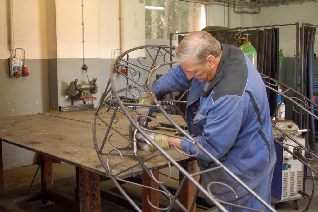 Ein großer Torbogen aus Metall wird von einem Mitglied in Arbeitskleidung zusammengeschweißt