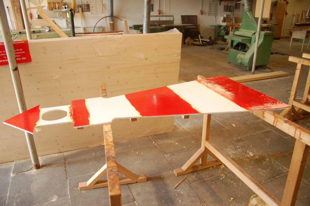 Ein Holzprojekt in der Werkstatt - Der Umriss eines rot - weißen Leuchtturmes aus Holz