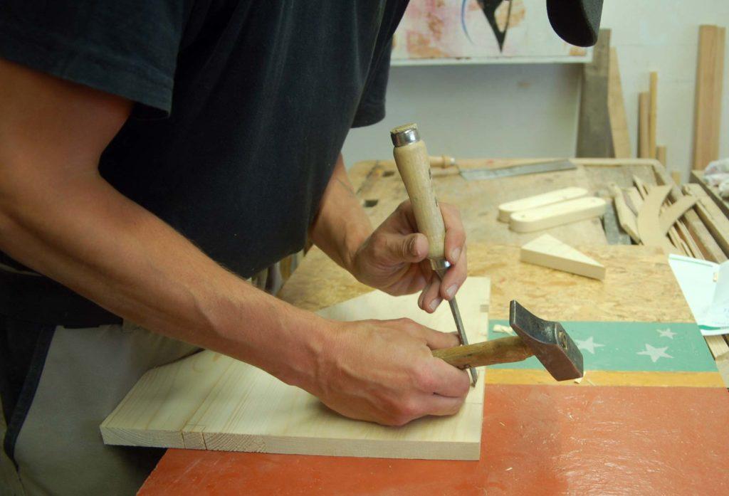 Ein Mitglied bei der Holzarbeit - Er hält einen Spachtel und einen Hammer und bearbeitet damit ein kleines zugeschnittenes Holzbrett