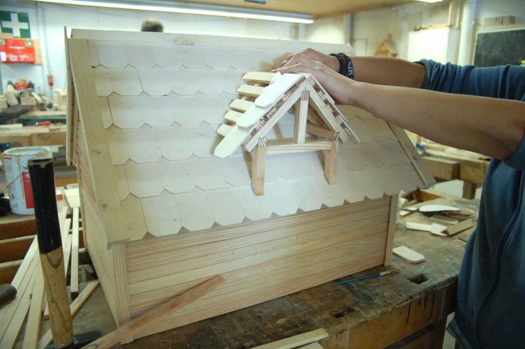 Ein Mitglied in der Werkstatt baut ein kleines Häuschen aus verschiedenen Holzmaterialien
