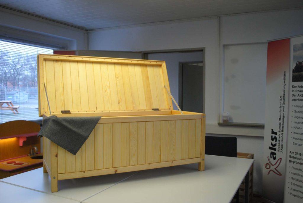 Eine geöffnete selbstgebaute Holzkiste mit Schanieren