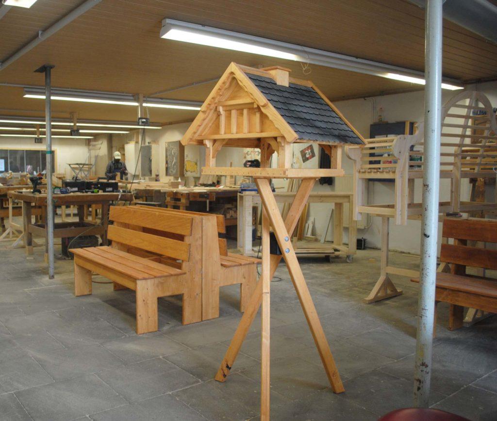 Verschiedene selbstgebaute Holzgegenstände in der Werkstatt, darunter: Holzbänke und ein filligranes Vogelhäuschen aus Holz