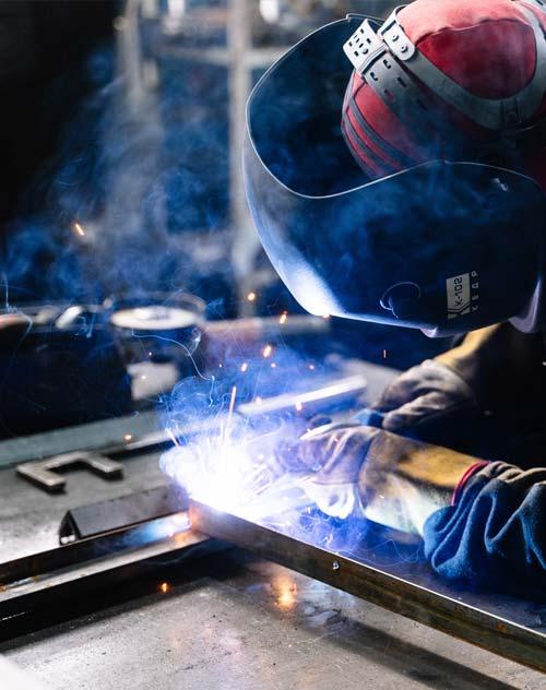 Ein Mann in Sicherheitskleidung am Schweißen von Metallstäben